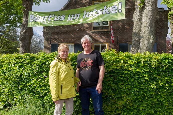 Wim Peters en echtgenote Majorie bij hun spandoek met tekst 'Buurt us un lutske!' dat ze in hun tuin hebben gehangen.