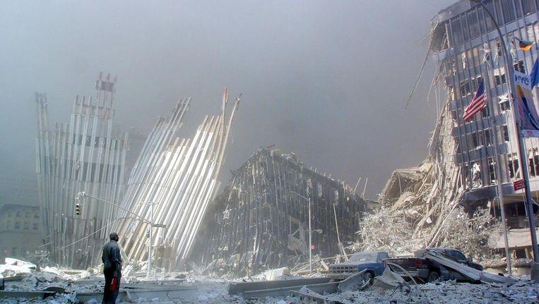 Een man staat bij de restanten van de Twin Towers als het stof neerdaalt. 2996 mensen vonden de dood, waaronder de 19 daders. Beeld epa