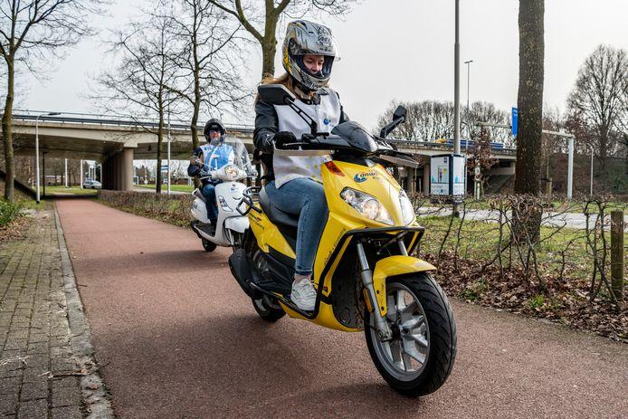 Kim Brocken kon eindelijk op examen voor haar scooterrijbewijs. Piet Mallens (achter) volgt nauwlettend haar verrichtingen.
