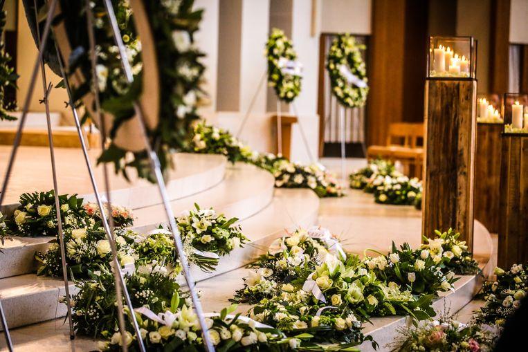 Een zee van witte bloemen lag vooraan in de kerk