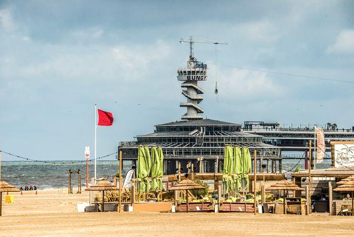 Rode vlaggen op strand van Scheveningen in de zomer.
