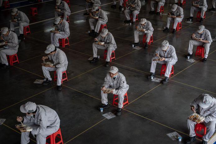 Arbeiders die in een autofabriek van Wuhan weer aan het werk zijn, houden zich bij de lunch keurig aan de voorschriften: op 1,5 meter afstand van elkaar en met de neuzen dezelfde richting uit.