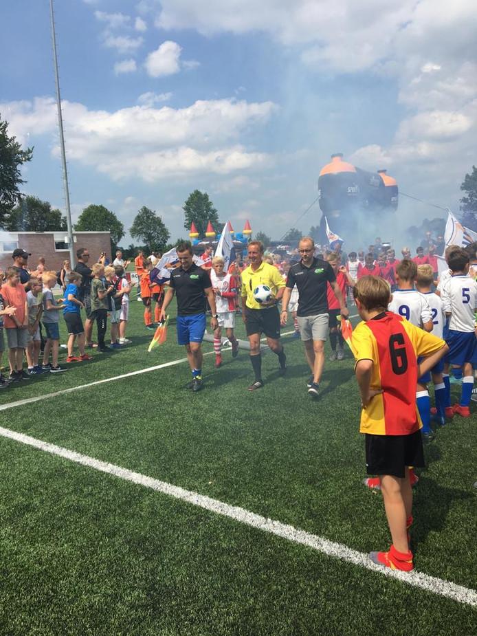 Scheidsrechter Harry Kunst en zijn assistenten - zijn zonen Job (links) en Jasper (rechts) - betreden het veld met achter hun de teams van finalisten Emmen en MVV'29.