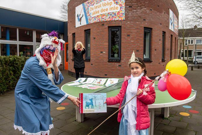 De 5-jarige Fayèn Kunstt krijgt het boek overhandigd door Elseline Withagen. Op de achtergrond directeur Ilse Elshof van De Aanloop.