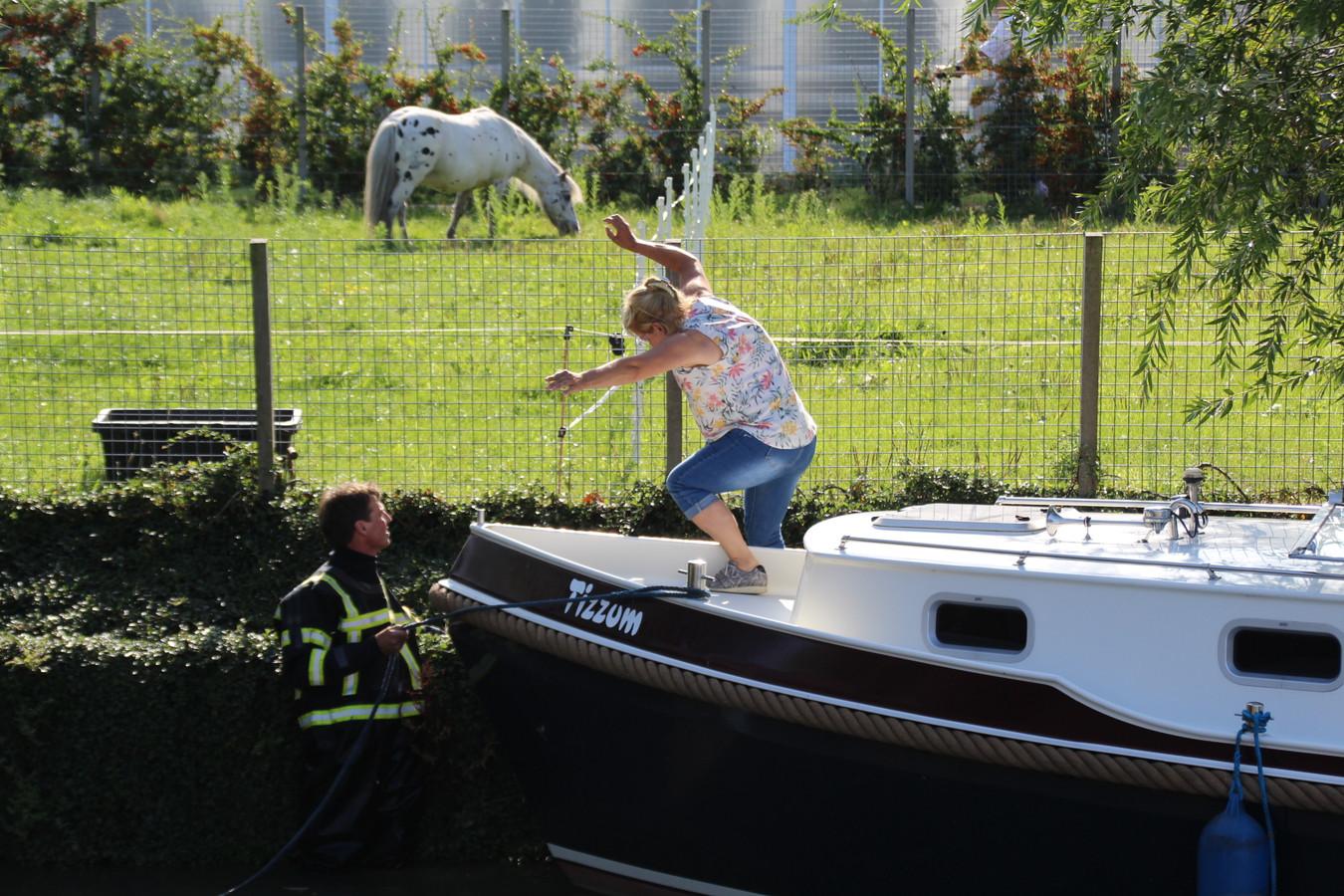 De vrouw op de boot werd door de brandweer van boord gehaald