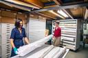 Elles van Vegchel (rechts) en medewerker Rosalie Swagemakers proberen orde te scheppen in het overvolle depot van het Textielmuseum.