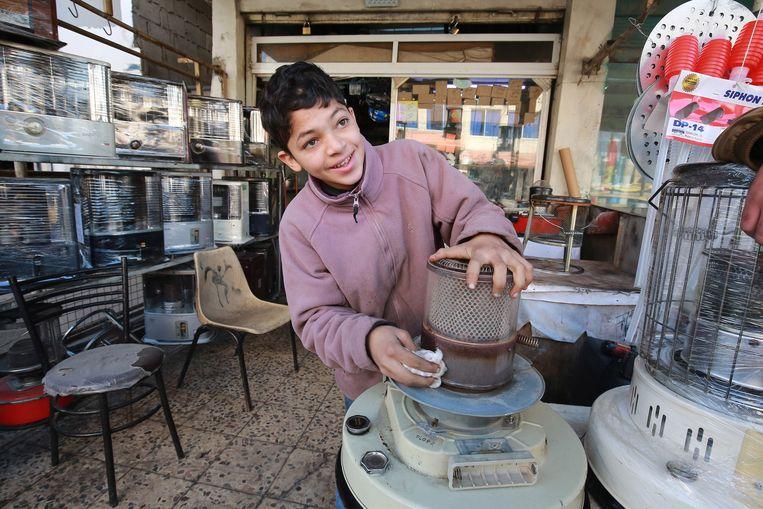 Omar, een Jordaanse tiener van 14, repareert een petroleumkachel op een werkplaats in Amman, op 10 januari 2021.  Beeld AFP