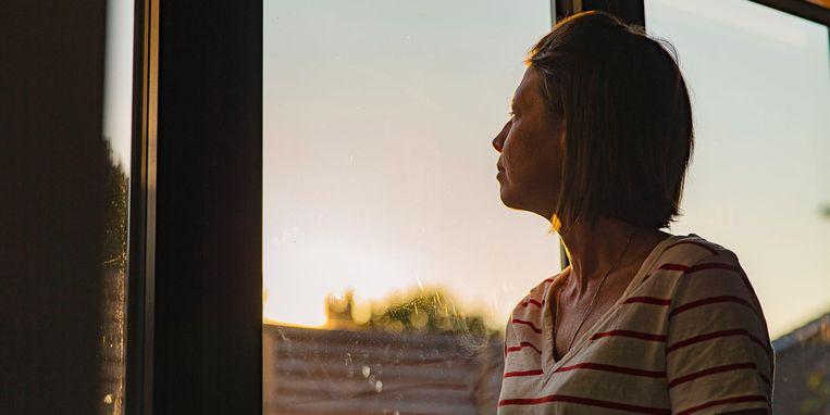 woman-looking-through-window-negative-emotion.jpg