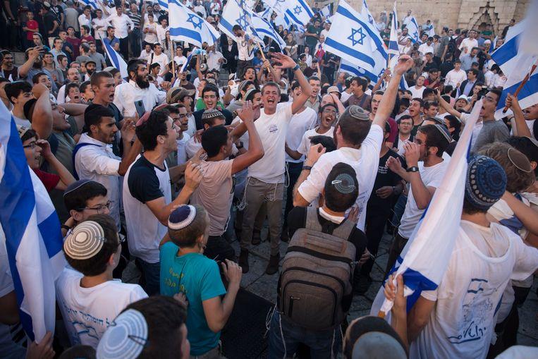 Israëlische ultranationalisten marcheren met hun vlaggen nabij de Damascus-poort. Beeld Getty Images