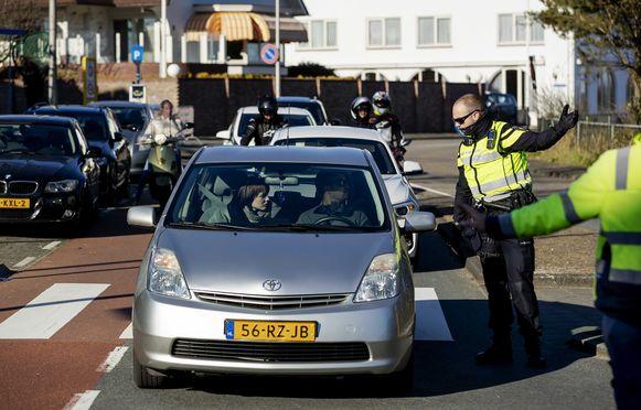 Nederlandse agenten houden mensen tegen op de toegangswegen naar het strand van Noordwijk nabij de universiteitsstad Leiden. Door het zonnige weer trekken veel mensen erop uit ondanks de coronacrisis.