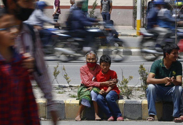 Een oma in Kathmandu houdt haar kleinkind stevig vast na alweer een nieuwe schok. Beeld EPA