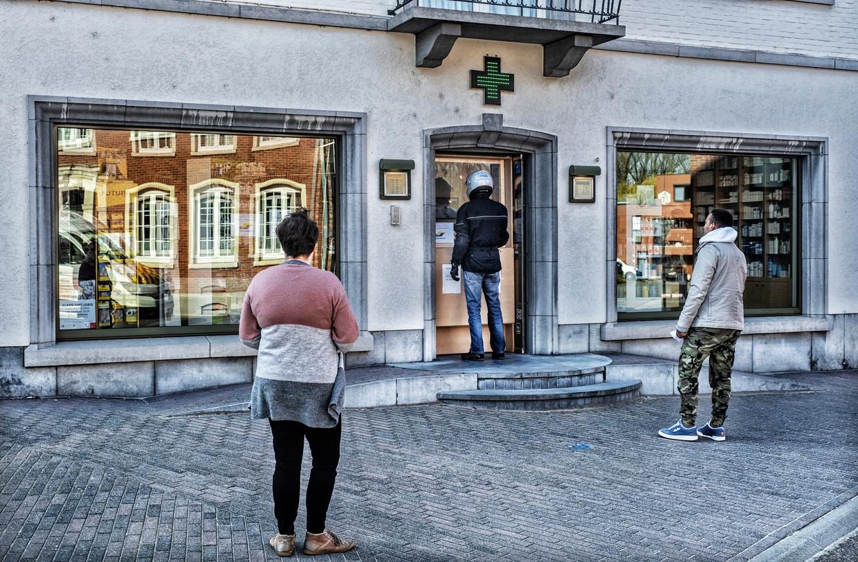 Klanten schuiven veilig aan bij een apotheek in het zwaar getroffen Alken. Beeld Tim Dirven