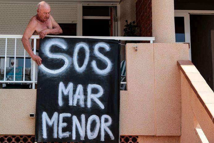 Un homme attache une bannière sur sa terrasse à Puerto Bello de la Manga, près de Murcie, le 25 août 2021.