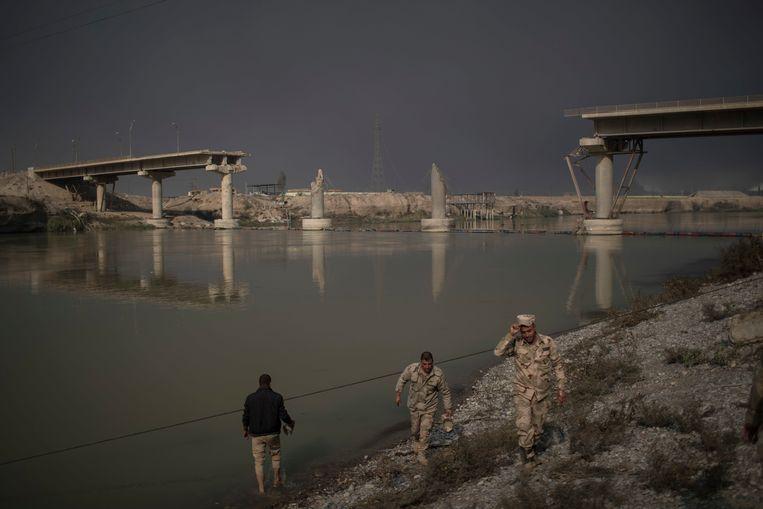 Iraakse soldaten bij een verwoeste brug over de Tigris, Irak. Beeld AP