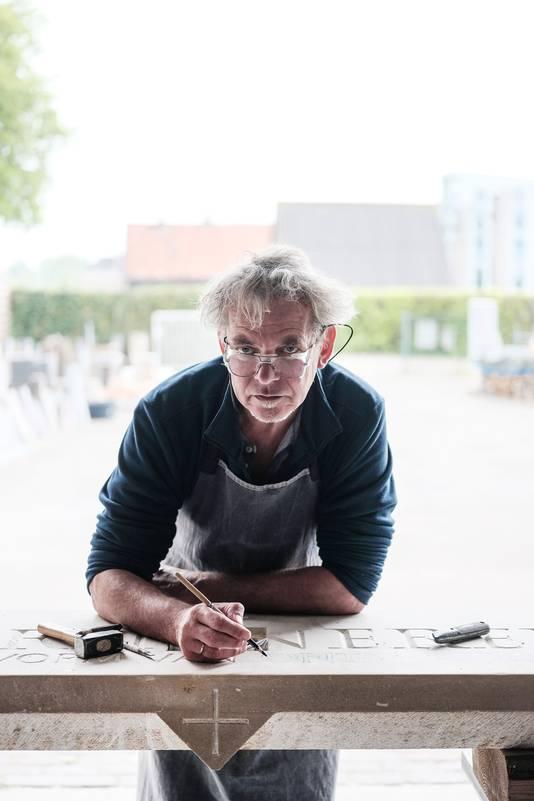 Henk Welling maakt letters in steen.