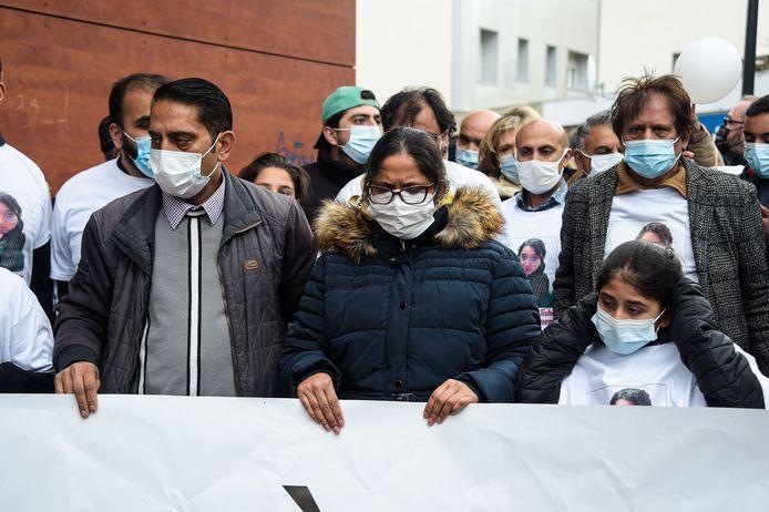 De moeder van Alisha, omringd door familie tijdens de witte mars