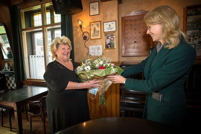 Staatssecretaris Mona Keijzer heeft een bloemetje meegenomen voor Christianne de Beer, die 40 jaar achter de toog staat in Het Chaamsche Wapen.