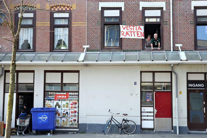 Mirjam en Edwin kijken uit op de Martinus Steijnstraat. Het spandoek tegen corporatie Vestia hangt er al maanden.