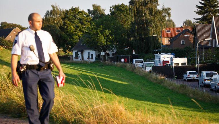 Een politieagent loopt op de dijk bij de woning in het Gelderse dorp Kekerdom waar drie lichamen zijn gevonden. Beeld anp