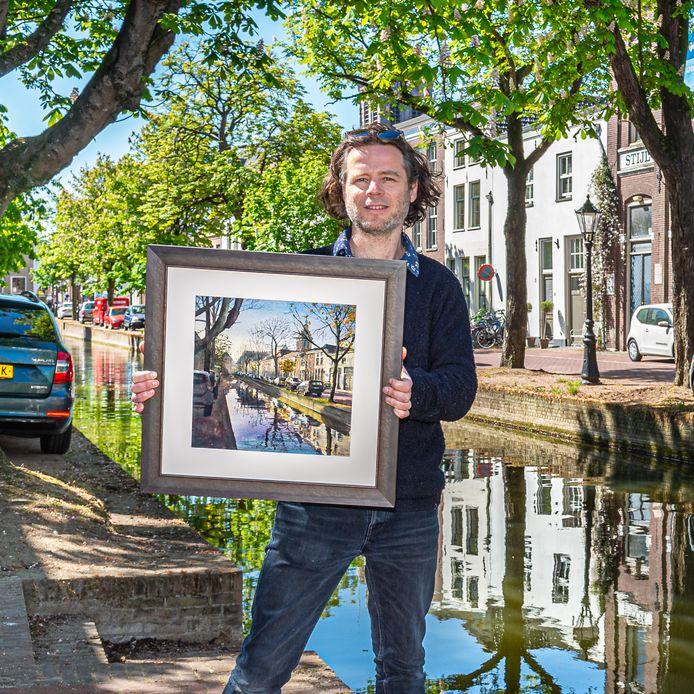 Kunstschilder Titus Meeuws toont één van zijn aquarellen van de binnenstad van Schoonhoven.