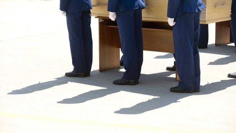 Oekraïense soldaten dragen de kisten van de slachtoffers tijdens een herdenkingsceremonie op het vliegveld van Charkov. Beeld epa