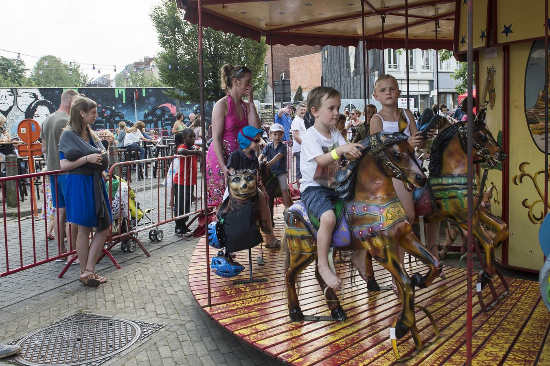 Kinderen genieten van een ritje op de paardenmolen.