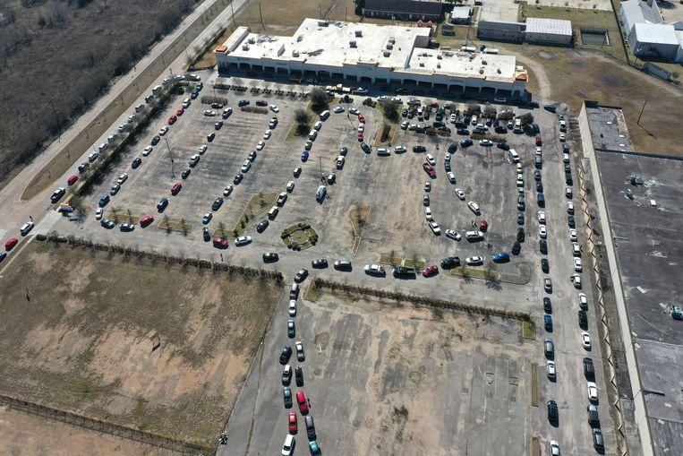 Auto's staan in een lange rij voor een locatie waar water wordt uitgedeeld in Houston. Beeld AFP