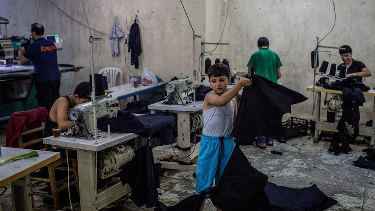 Syrische kinderen aan het werk in een kledingfabriek in Gaziantep. Beeld Getty Images