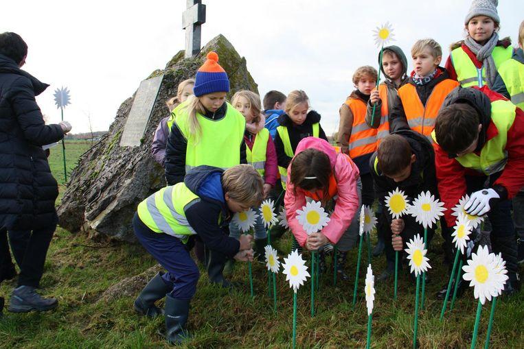 Leerlingen van de vrije basisschool van Merkem planten papieren madeliefjes bij het monument.