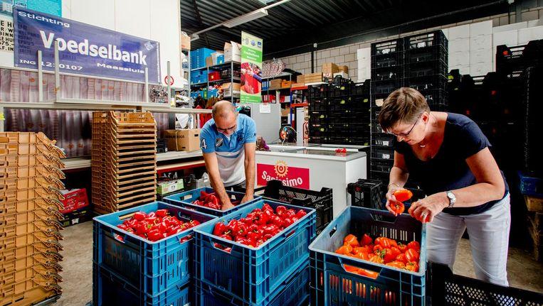 Vrijwilligers sorteren paprika's bij de voedselbank. Beeld anp