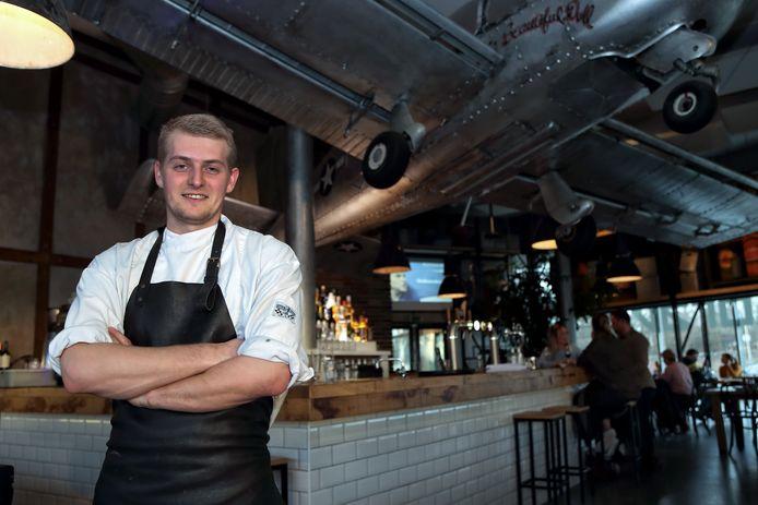 Chef-kok Rien Mertens met het oude vliegtuig hangend boven zijn hoofd.