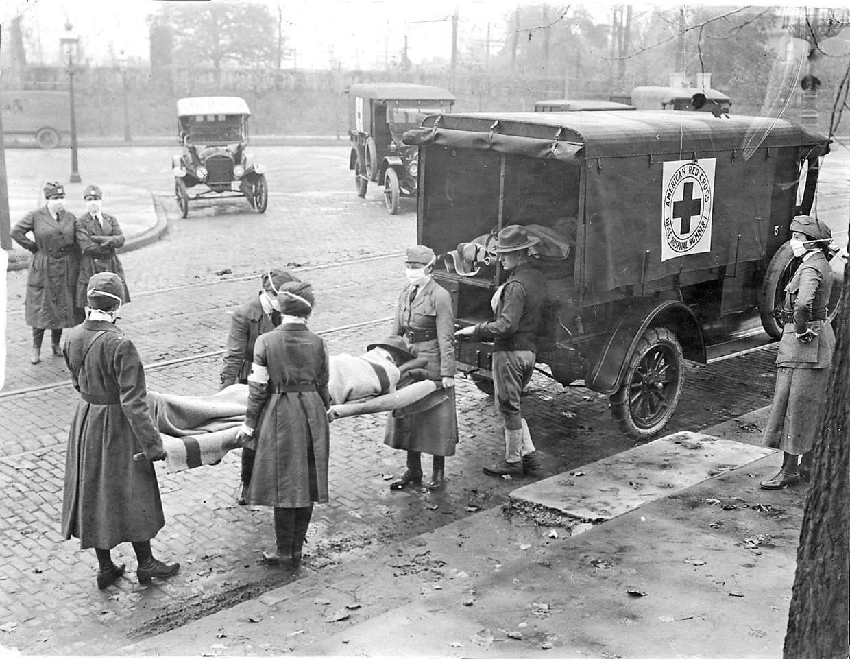 Leden van het Amerikaanse Rode Kruis vervoeren een slachtoffer van de Spaanse griep in St. Louis in 1918. Beeld TNS via Getty Images