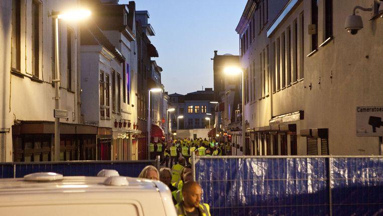 Politie en justitie Den Haag vorig jaar tijdens een actie tegen internationale mensenhandel. De Doubletstraat, waar 164 prostitutieramen zitten, werd afgesloten en in zedenzaken gespecialiseerde agenten voerden uitgebreide controles uit. Beeld ANP