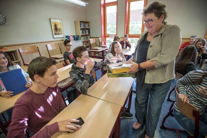 Mentor Gerda Vervelde haalt de mobieltjes op.