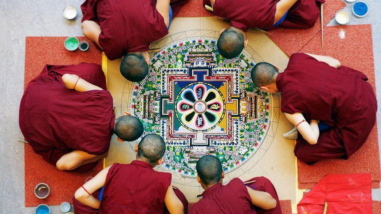 De monniken buigen zich dagenlang over het kunstwerk. Beeld Marlies Bosch