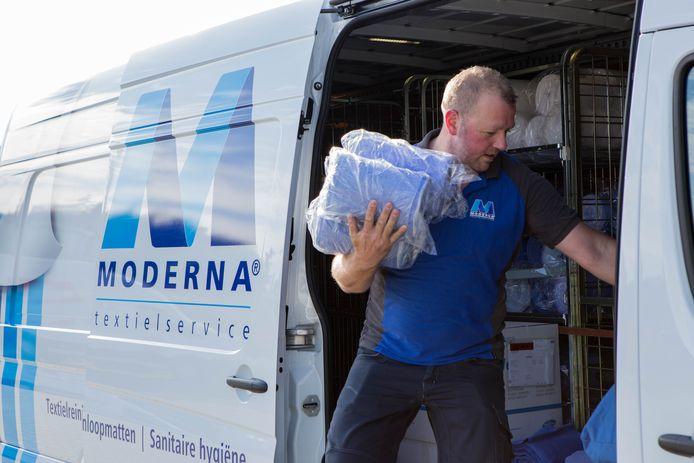 Een medewerker van wasserij Moderna haalt spullen - nee, geen vaccins - uit zijn busje.
