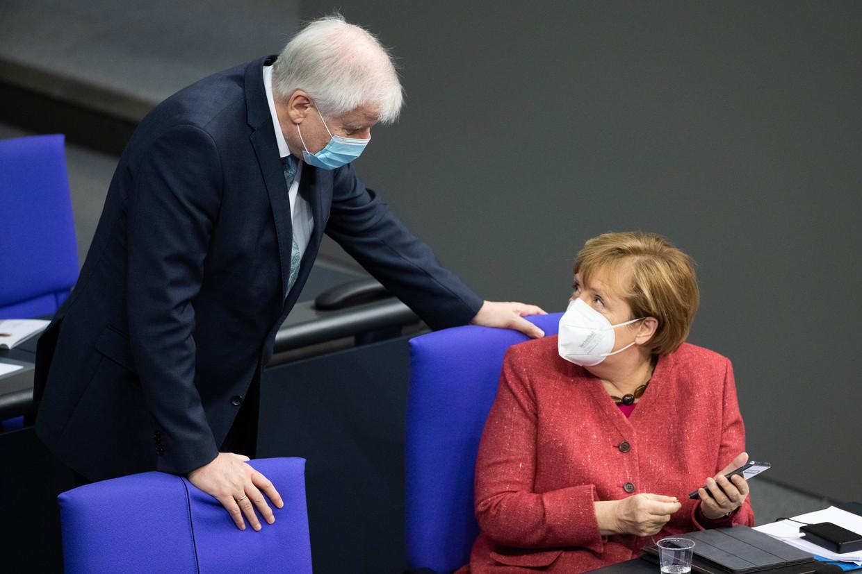 De Duitse Minister van Binnenlandse Zaken, Horst Seehofer, in gesprek met Bondskanselier Angela Merkel. Beeld EPA