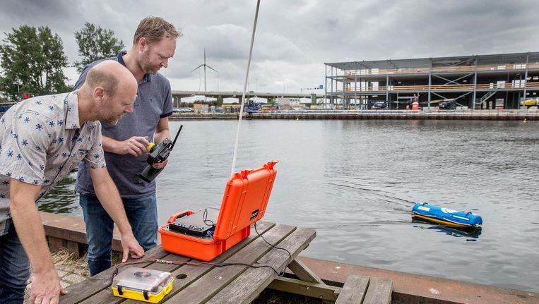 Arnoud van der Wal (l) en Lennaert Zonneveld van Waternet testen Emily in de Moezelhaven. Beeld Jean-Pierre Jans