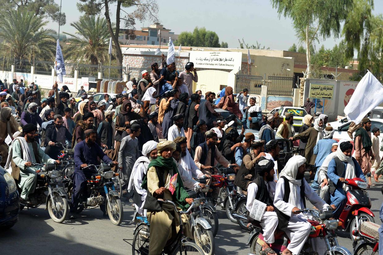 Afghanen die de Taliban steunen zwaaien met vlaggen van de beweging in Kandahar om het vertrek van de Amerikanen te vieren.  Beeld AFP