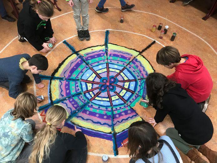 Kinderen van groep 7 van de Rudolf Steinerschool hebben met de hand een mandala van gekleurd zand gemaakt, die nu symbool staat voor de verbondenheid van de klas.