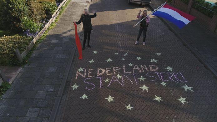 Ella van Kempen en Vera Louws hebben zondagochtend hun straattekening in de Oude Koudekerkseweg  in Middelburg nog eens overgedaan, nadat de regen zaterdagmiddag hun hele grote ster had weggespoeld.