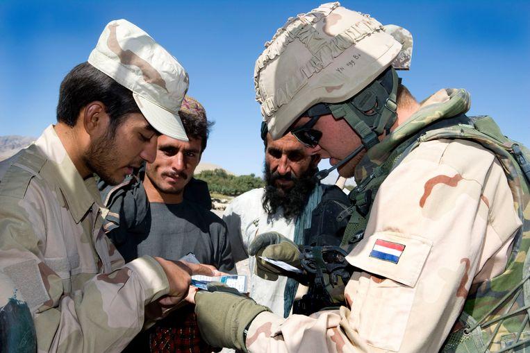 Nederlandse militairen patrouilleren in de Afghaanse stad Tarin Kowt.  Beeld ANP