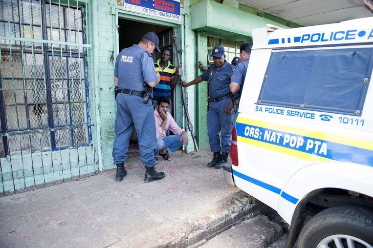 Een winkeleigenaar voor zijn geplunderde winkel in Johannesburg Beeld afp