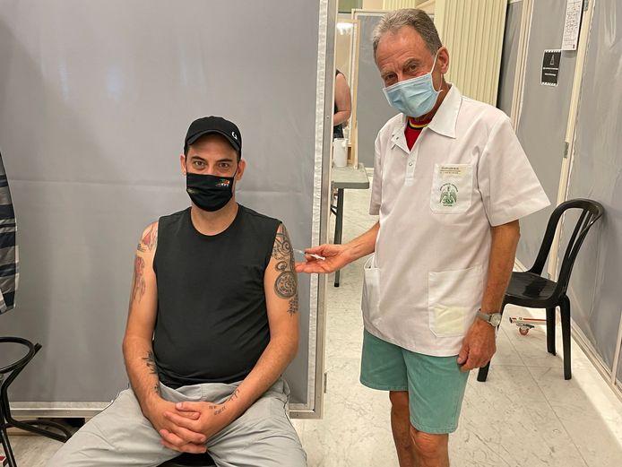 """Vader Willy Lefevere vaccineert zijn eigen zoon Dieter in Oostende. """"In mijn linkerarm, hé, je komt niet aan mijn tatoeage van KVO"""", glimlacht Dieter."""