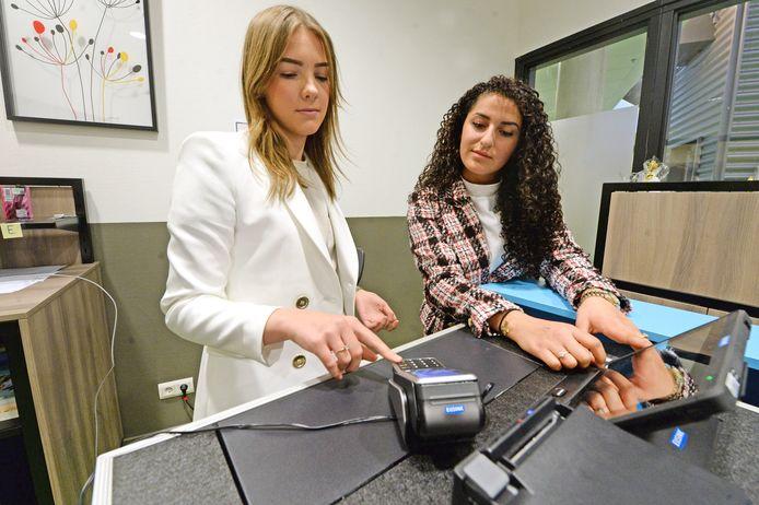 Praktijkexamens voor vmbo op het Bonhoeffer College in Enschede. Jolita Gabriël (rechts) en Puck Bakker doen een rollenspel in een denkbeeldige winkel.