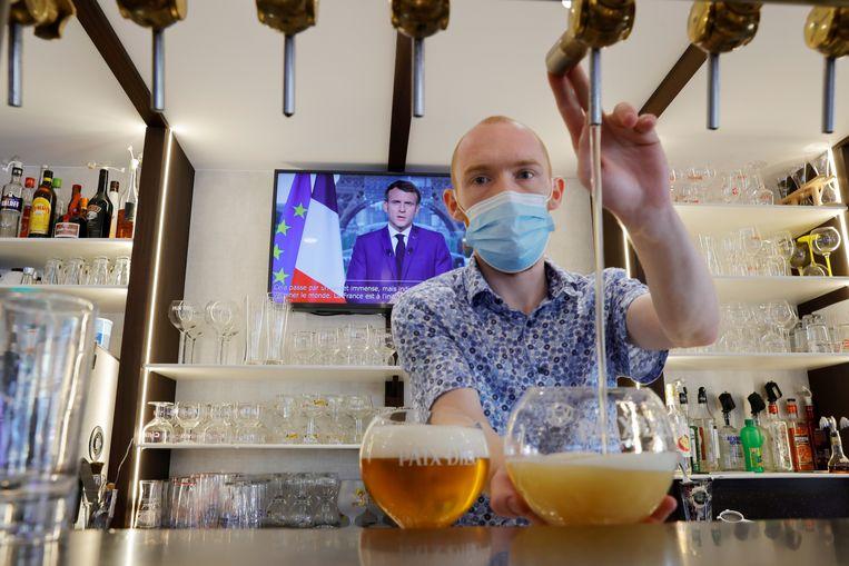 Een barman in Cambrai tapt bier met de televisietoespraak van president Macron op de achtergrond. Beeld Reuters