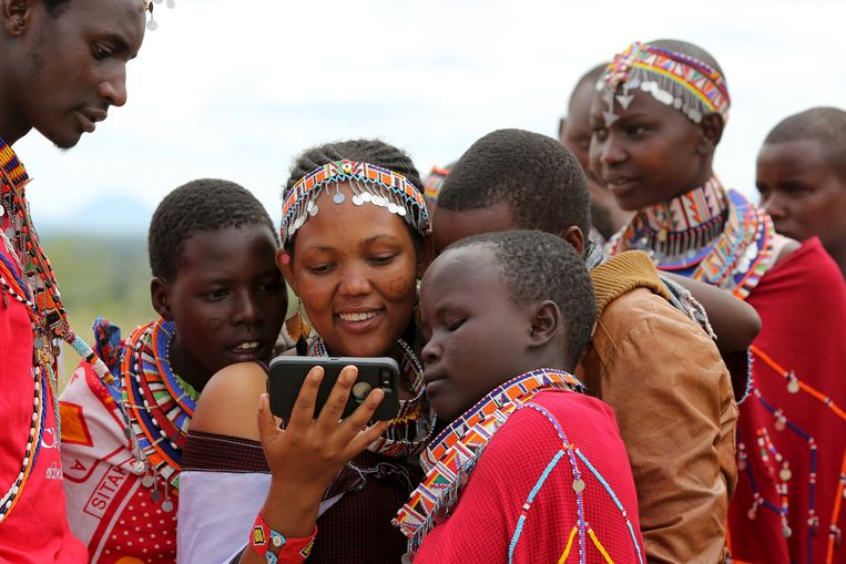 Maasai girls and a man watch a video on a mobile phone prior to the start of a social event advocating against harmful practices such as Female Genital Mutilation (FGM) at the Imbirikani Girls High School in Imbirikani, Kenya. Beeld REUTERS