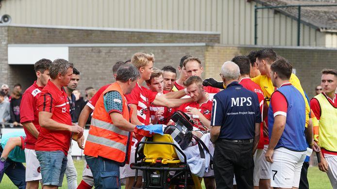 Clinge-speler Sven d'Hooghe wordt getroost door zijn ploeggenoten, vlak voordat hij per ambulance het veld van Steen zal verlaten.
