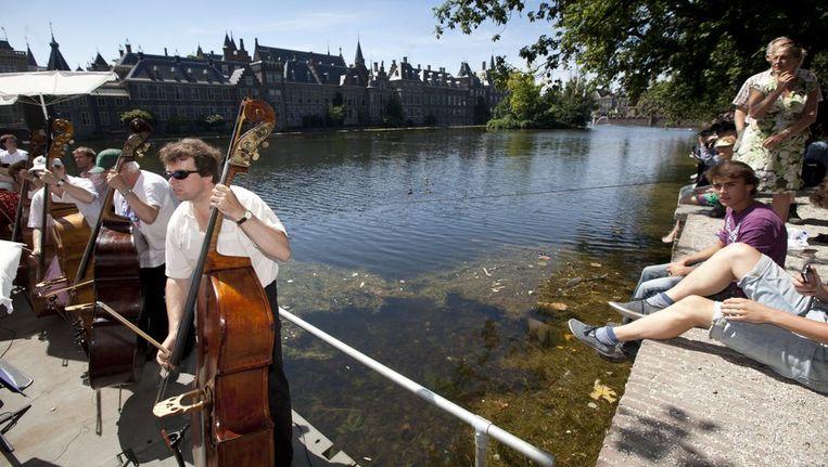 Musici uit verschillende beroepsorkesten, ensembles en koren spelen maandag samen op een ponton in de Hofvijver in De Haag. Zij protesteerden tegen de geplande bezuinigingen op cultuur. Beeld anp