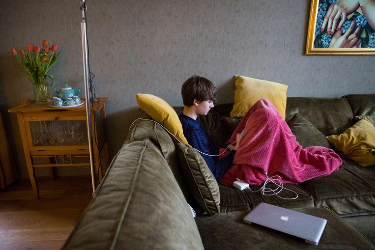 Sam, 15 jaar, zit op de bank en volgt online les op zijn mobieltje. Beeld Arie Kievit